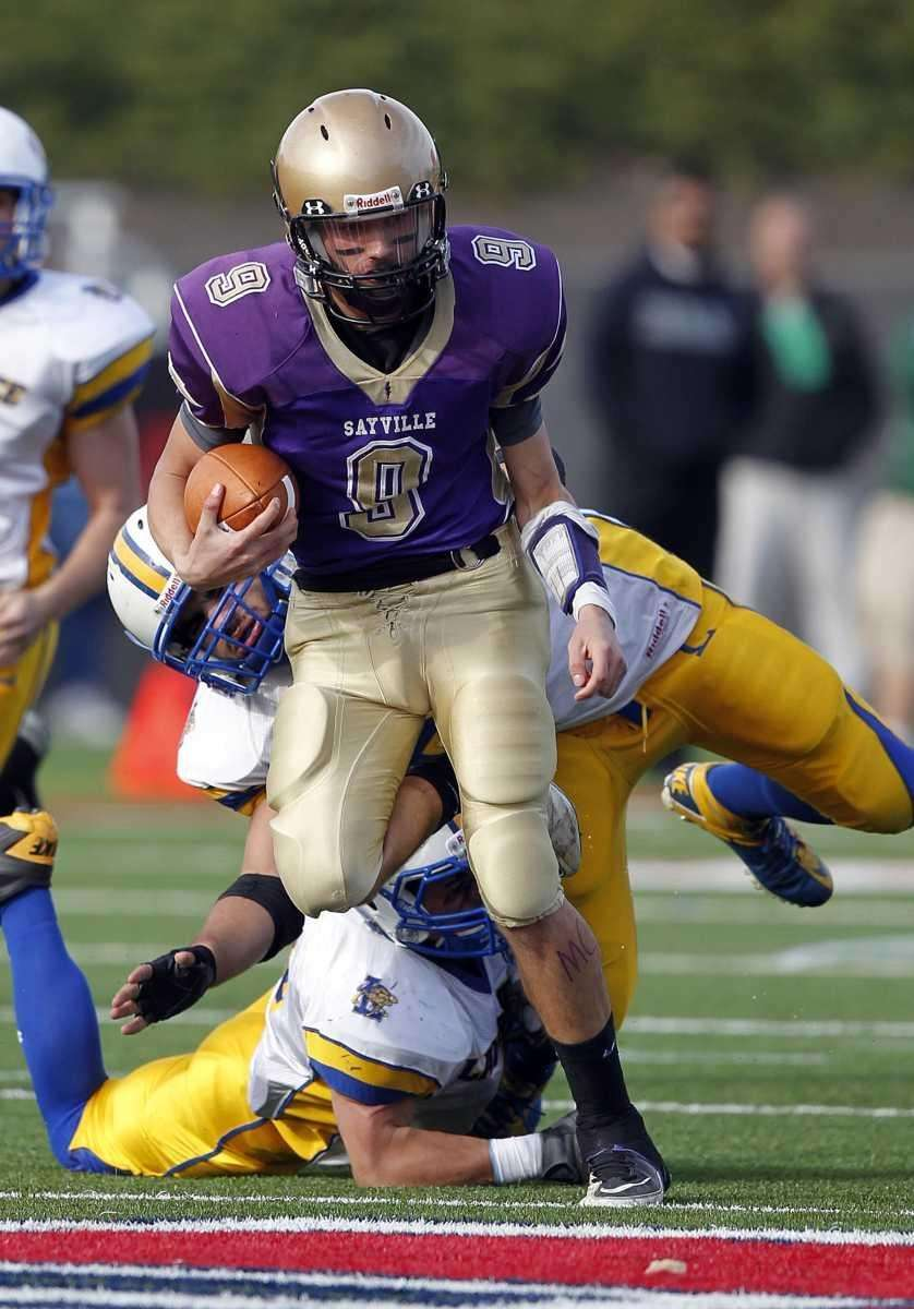 Sayville quarterback Steve Ferreira (9) breaks tackles at