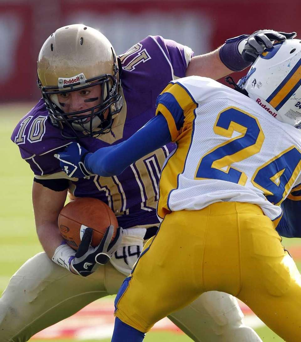 Sayville's Thomas Hannan (10) evades the tackle attempt