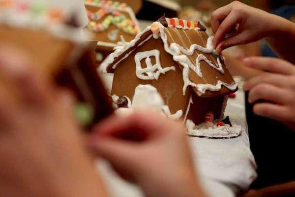 A gingerbread house is decorated at a workshop