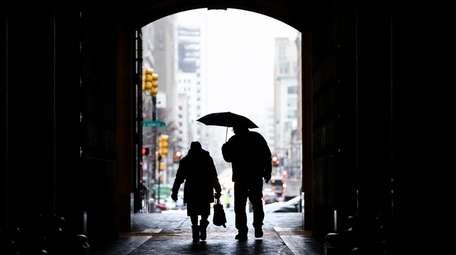 Pedestrians pass beneath City Hall in Philadelphia on