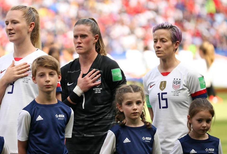 United States' Megan Rapinoe, right, stands with her