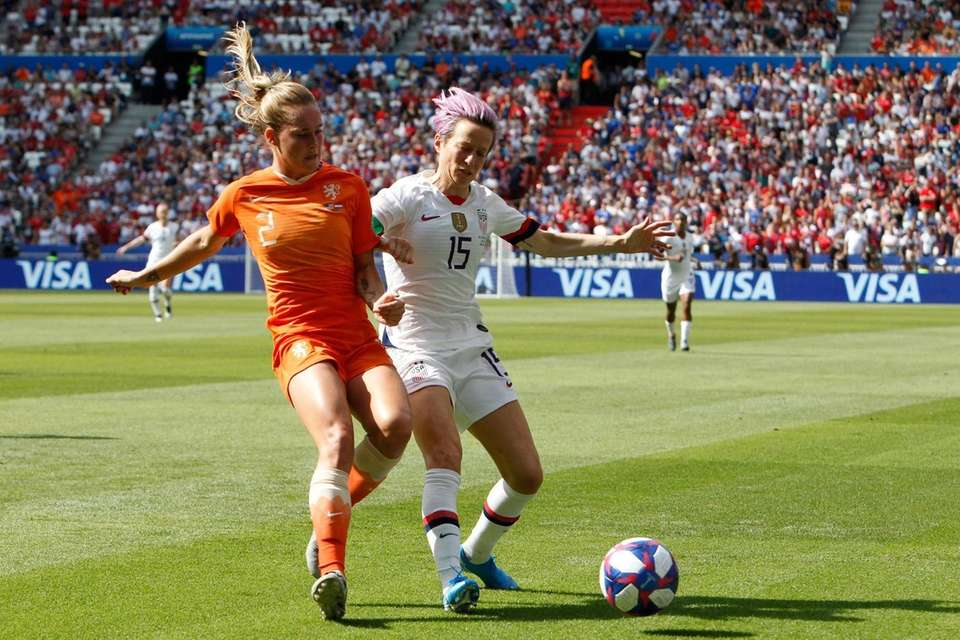 United States' Megan Rapinoe , right, fights for
