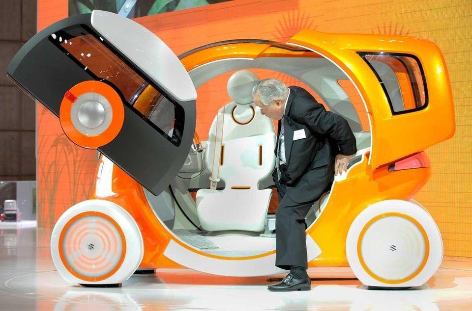 Osamu Suzuki, chairman of Japan's Suzuki Motor, inspects