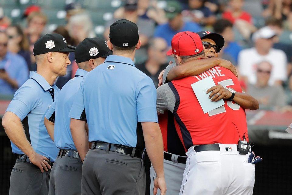 National League manager Dennis Martinez hugs American League