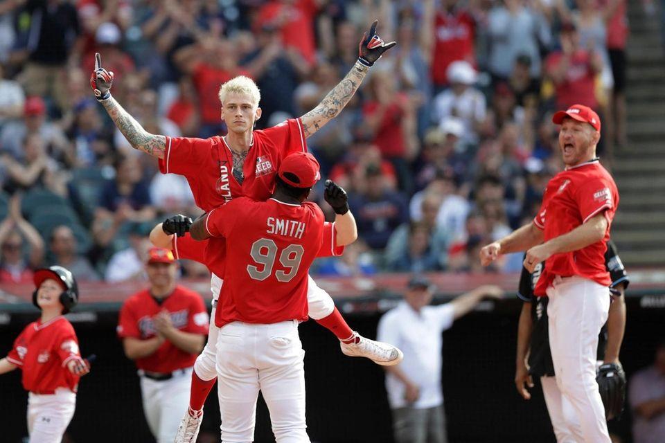 Machine Gun Kelly, top, celebrates with J.R. Smith