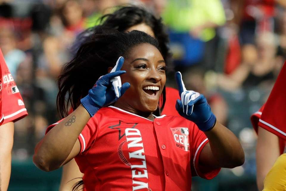 Simone Biles reacts after scoring during the MLB