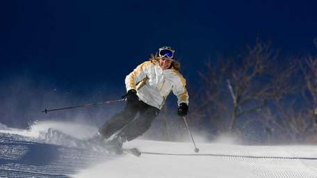 A woman skis down the groomed slope at