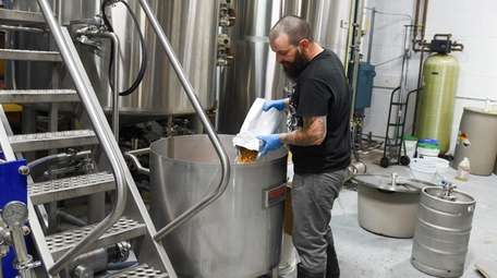 Paul Komsic, owner of Ghost Brewing, mixes in