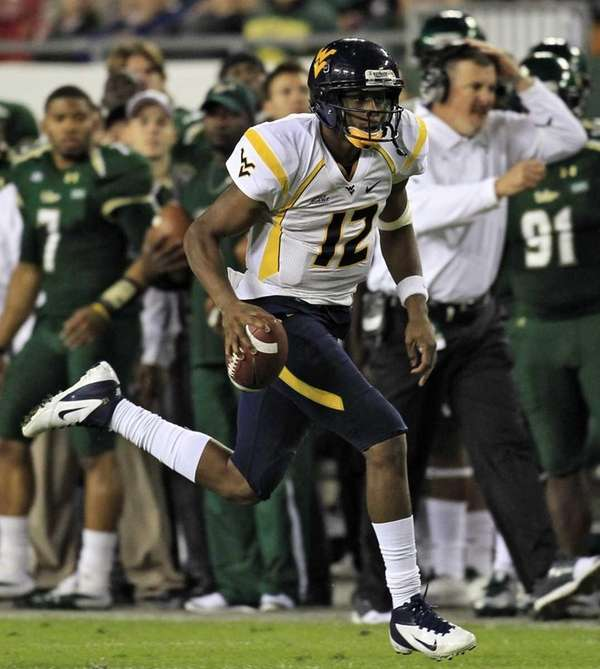 West Virginia quarterback Geno Smith (12) runs for