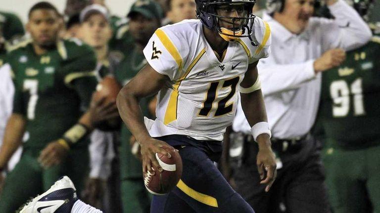 West Virginia quarterback Geno Smith (12) runs for