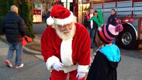 Santa Claus greets Natalie Moran, 8, of Stewart