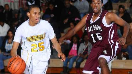 Uniondale's Aaron Cust, left, dribbles past Bay Shore