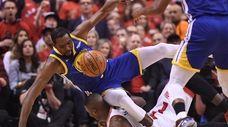 Kevin Durant, left, tumbles over Raptors center Serge