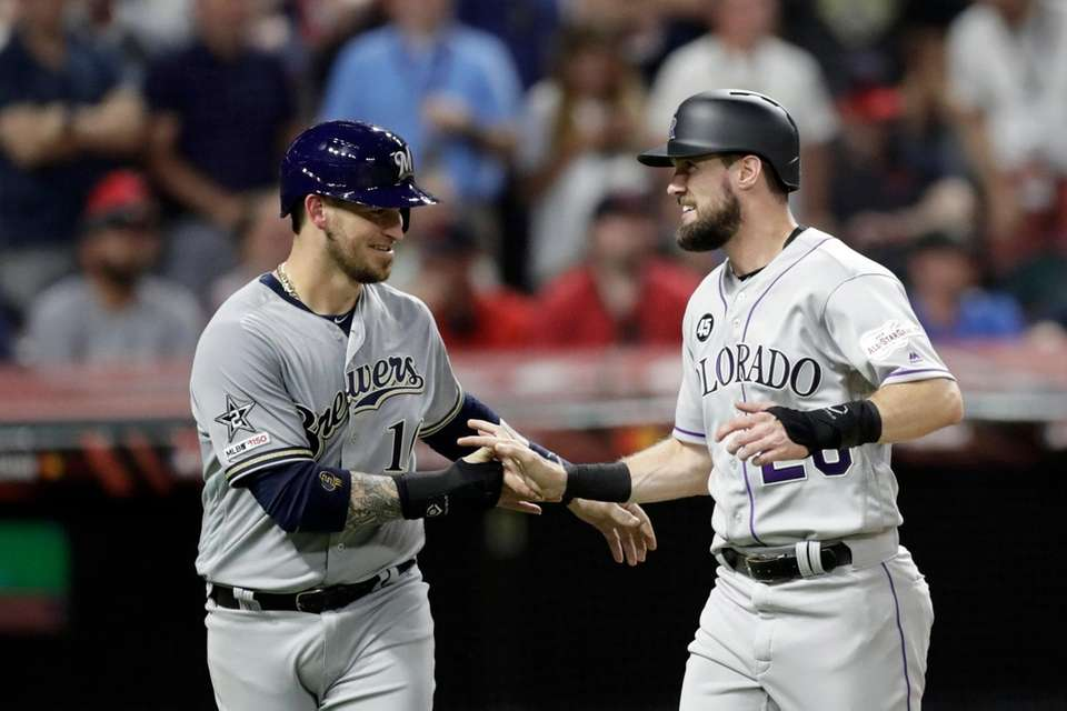 National League's Yasmani Grandal, left, of the Milwaukee