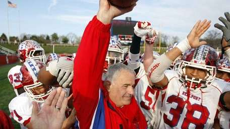 Bellport head coach Joe Cipp holds up the