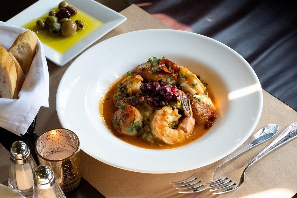 Shrimp and scallops over pesto risotto with tomato-saffron