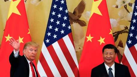 President Donald Trump waves next to Chinese President
