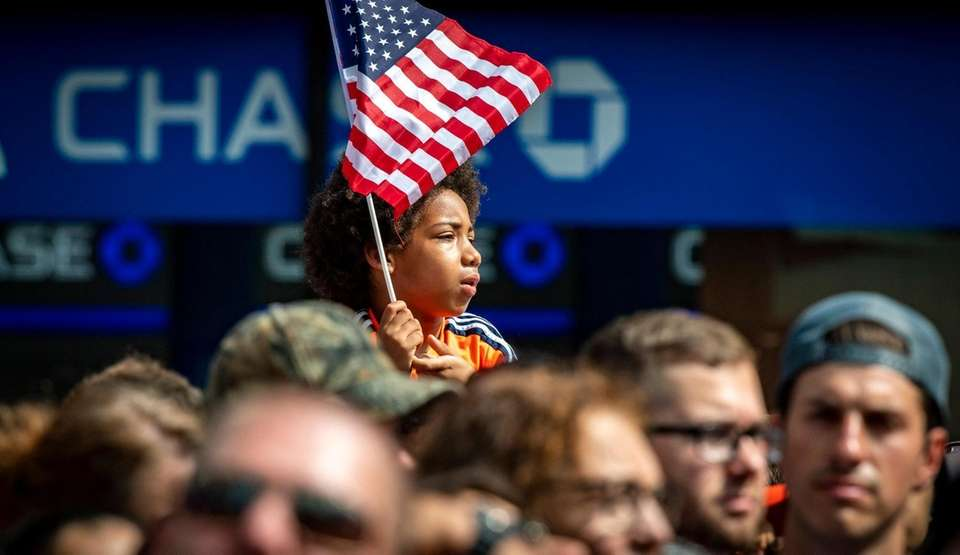 A young boy holding the American flag during