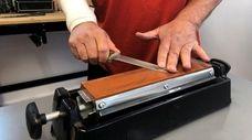 Richard De Vito, Sr. finishes sharpening a knife