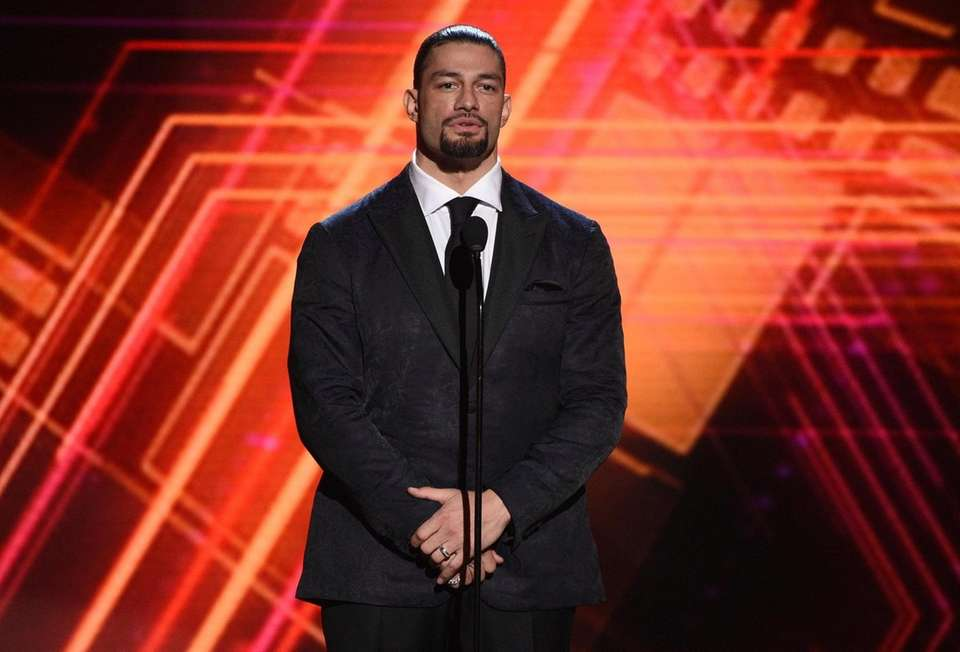 Roman Reigns presents the best coach award at