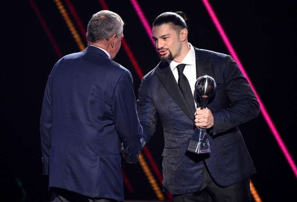 Roman Reigns, right, presents the best coach award