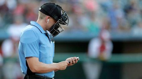 Home plate umpire Brian deBrauwere checks an iPhone