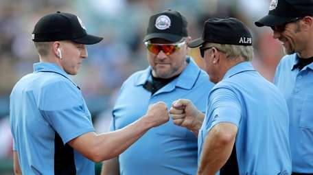 Home plate umpire Brian deBrauwere, left, huddles with