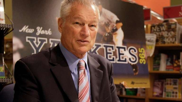 Former New York Yankees pitcher Jim Bouton signs