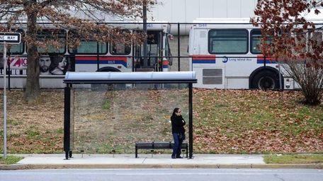 A woman waits at a bus stop along