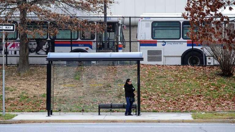 A woman waits at a bus stop along