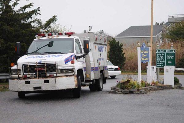 A police vehicle drives through an Oak Beach