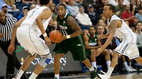 Wagner guard Chris Martin dribbles against UConn defenders.
