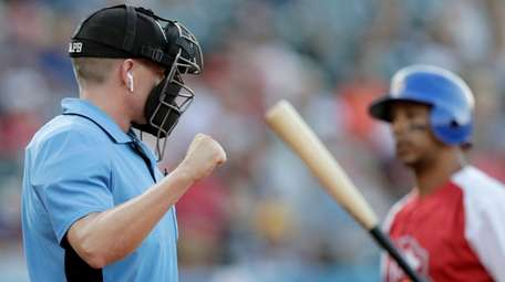 Home plate umpire Brian deBrauwere, left, calls a