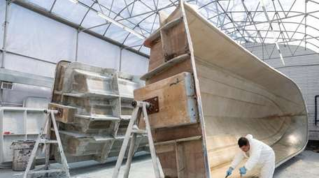 Santos Garcia spreads fiberglass resin on a hull
