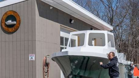 Steiger Craft employees move a boat to the