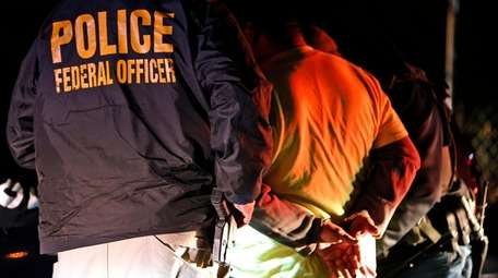 U.S. Immigration and Customs Enforcement agents detain a