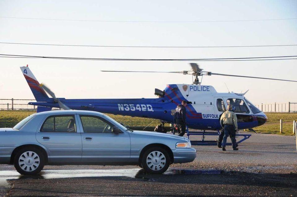 Police board a helicopter near Oak Beach as