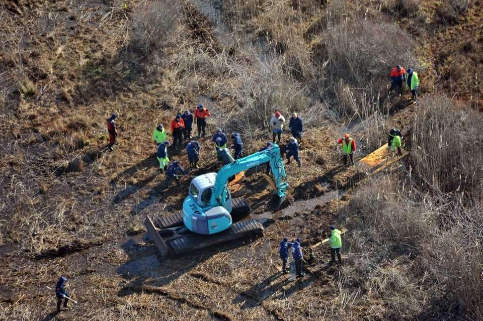 Police officers and an excavator are seen from
