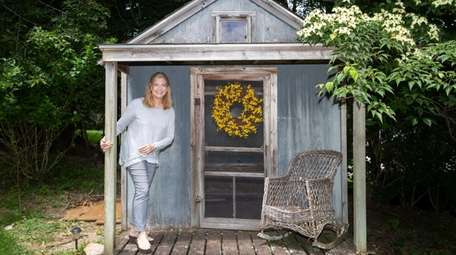 Barbara Daddino by a backyard shed on her