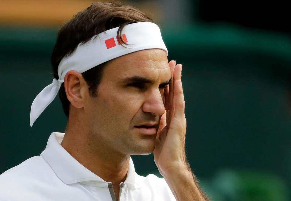 Switzerland's Roger Federer wipes his face during a