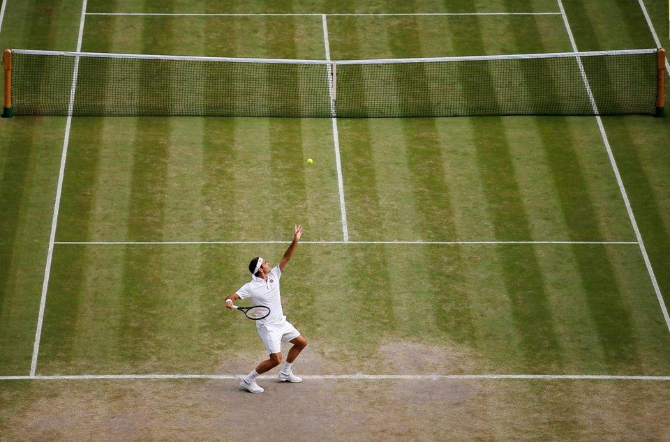 Switzerland's Roger Federer serves to Spain's Rafael Nadal