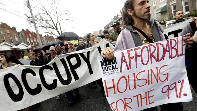 Occupy Wall Street activists march past foreclosed homes