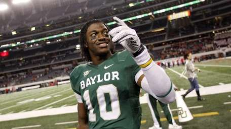 Baylor quarterback Robert Griffin III (10) waves to