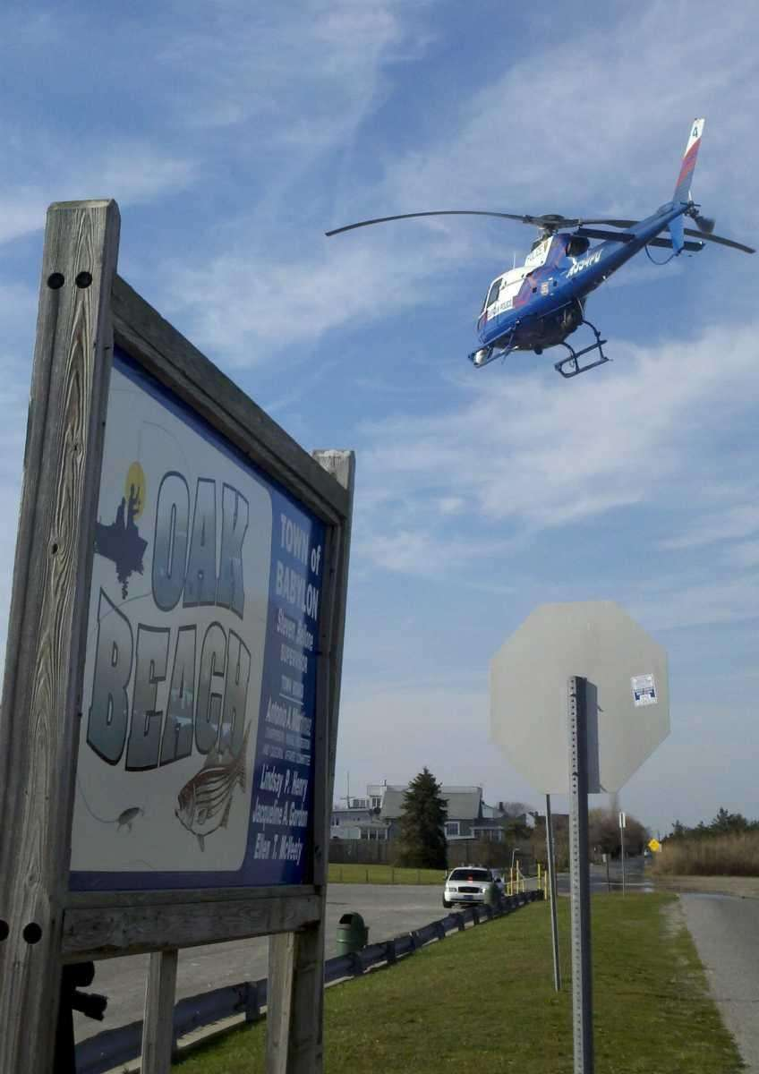 A Suffolk County helicopter circles over Oak Beach