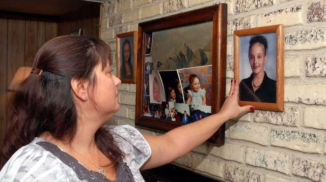 Lynn Barthelemy looks at a photograph of her