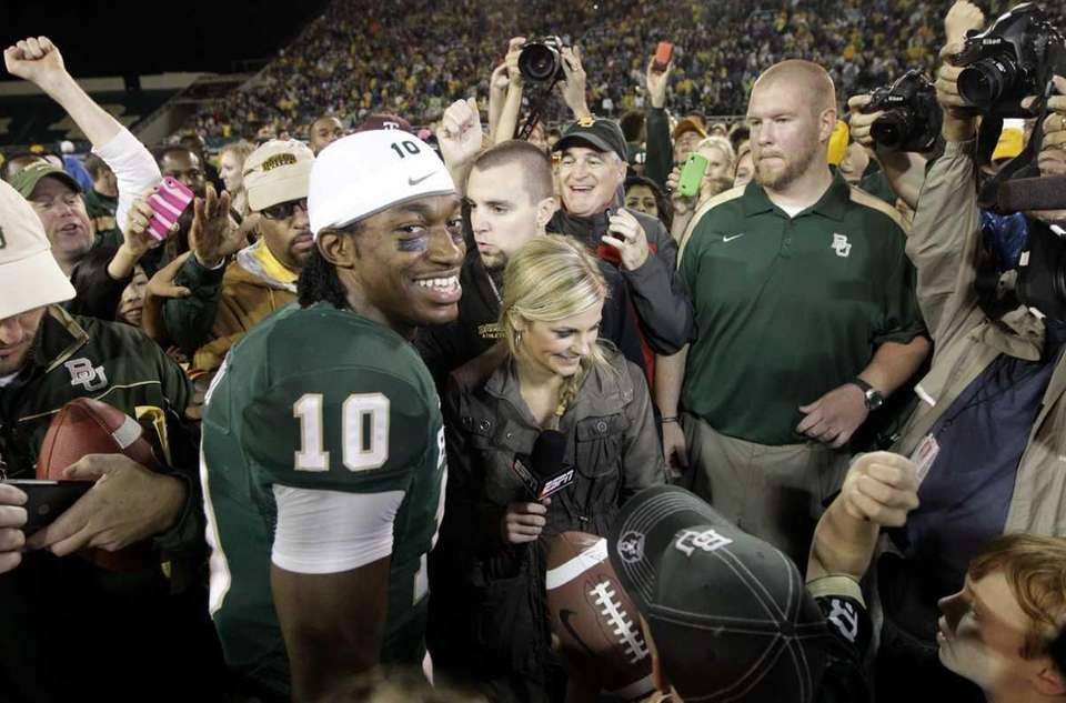 Baylor quarterback Robert Griffin III stands surrounded on