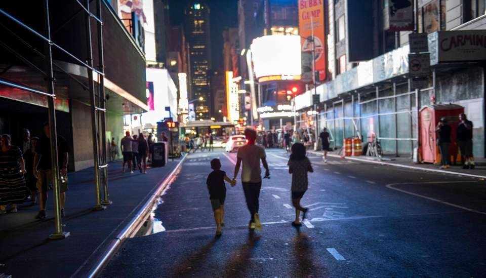 Pedestrians walking towards lights of Times Square through