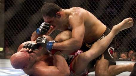 Antonio Rodrigo Nogueira, top, trades blows with Tito