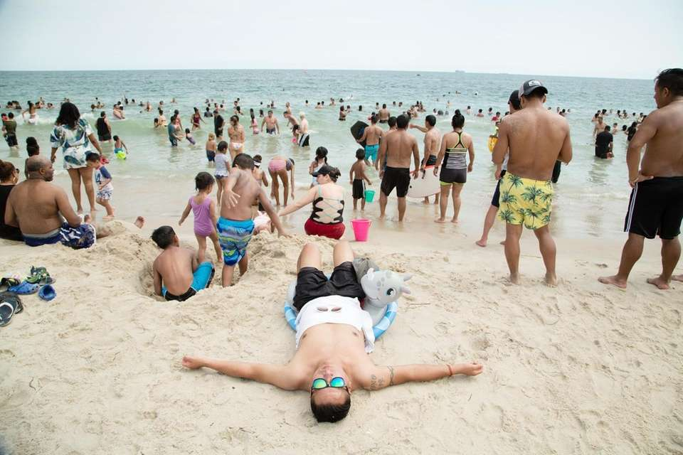 Beachgoers take to the water and sand at