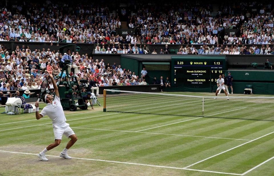 Switzerland's Roger Federer, left, serves to Serbia's Novak